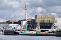 Le catamaran Groupama devant l'ancienne base de sous marins de Lorient