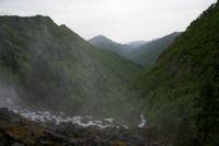 La vallee boisee de la riviere d'Ars embrumee par les embruns de la cascade