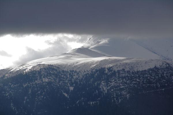 Les pentes enneigées menant au Pic de Cabaliros dans les nuages menaçants