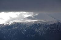 Les pentes enneigees menant au Pic de Cabaliros dans les nuages menacants