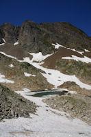 Un petit laquet encore partiellement gele domine par le Pic Sarroa